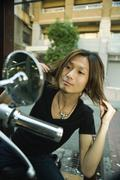Stock Photo of Young Japanese man seated on motorbike, fixing hair in side-view mirror