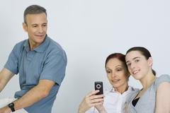 Family sitting together, parents looking at cell phone, daughter smiling at Stock Photos