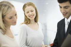 Three professionals looking at folder together, focus on woman smiling in center - stock photo