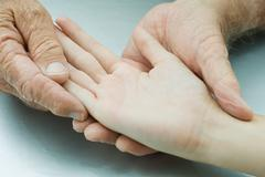 Man holding young person's hand, palm facing up, cropped view Stock Photos