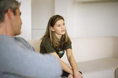 Teenage girl sitting on sofa contemplatively looking away, father in foreground Stock Photos