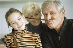 Young girl with grandparents, grandfather using girl's braid to imitate mustache Stock Photos