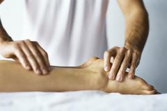 Therapist treating patient's foot with acupressure Stock Photos