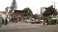 Wide Angle Shot of pedestrians and vehicles at a Gas Station Stock Footage