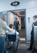Man with traveler in wheelchair at boarding gate - stock photo