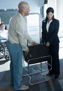 Man checking dimensions of carry-on bag at boarding gate Stock Photos