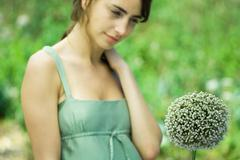 Stock Photo of Woman looking at allium flower