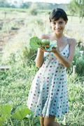 Young woman holding up fresh produce in cabbage leaves, smiling at camera Stock Photos