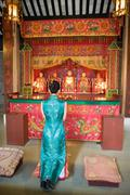 Young woman wearing traditional Chinese clothing, kneeling in front of shrine Stock Photos