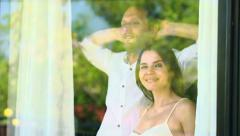 Couple in love unveil curtains by the window HD Stock Footage