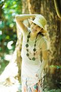 Young woman standing in woods, holding sunhat on head, smiling at camera - stock photo