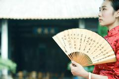 Young woman wearing traditional Chinese clothing, holding fan, looking up Stock Photos