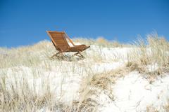 Deck chair in dunes Stock Photos