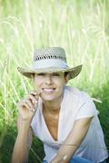 Stock Photo of Woman in field, blade of grass between lips, looking at camera
