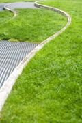 Stock Photo of Metal grate and concrete curves in grass