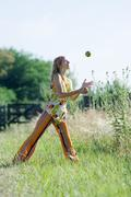 Young woman standing in field with legs apart, juggling apples - stock photo