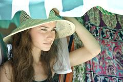 Young woman wearing straw hat, looking away - stock photo