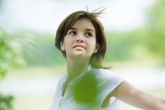 Young woman standing outdoors, being blown by breeze, looking up Stock Photos