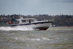 speedboat powering through waves on the solent - stock photo
