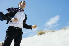 Businessman running across sand dune, low angle view Kuvituskuvat