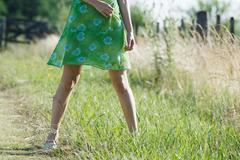 Young woman standing in rural field with legs apart, cropped view Stock Photos