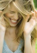 Young woman lowering head, shutting eyes and laughing with hands up Stock Photos