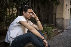 Sad, unhappy young man outdoor, sitting on pavement Stock Photos