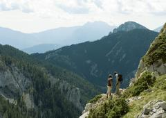 Hikers looking at mountainous landscape - stock photo