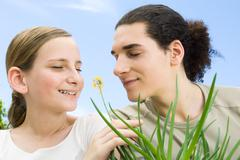 Young man and preteen girl smelling flowering aloe plant, eyes closed - stock photo