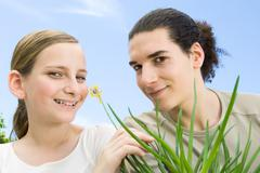 Young man and preteen girl with flowering aloe plant, smiling at camera Stock Photos