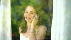 Young woman talking on cellphone by the window HD Stock Footage