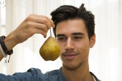 Young man holding a large ripe yellow pear Stock Photos