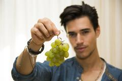 Young man holding a large delicious ripe bunch of grapes Stock Photos