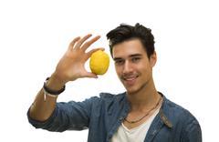 smiling young man holding a fresh yellow lemonin his hand - stock photo