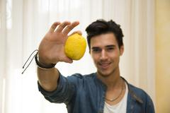 Young man holding a large delicious ripe lemon Stock Photos