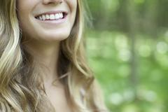 Stock Photo of Young woman with toothy smile, cropped