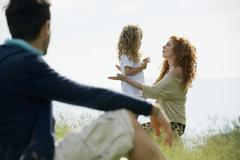 Mother talking with young daughter outdoors, father watching from foreground - stock photo