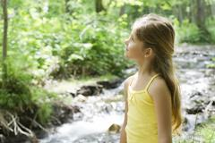 Girl standing beside stream, looking up in awe Stock Photos