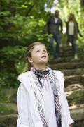 Girl standing in woods, looking up in awe Stock Photos