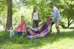 Family preparing for picnic in meadow Stock Photos