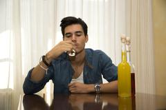 young man sitting drinking alone at a table with two bottles of liquor - stock photo