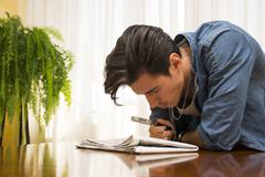 Young man reading with a magnifying glass Stock Photos