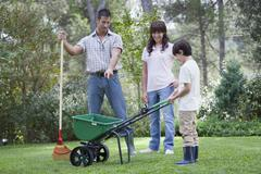 Father and two children working together in yard Stock Photos