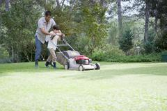 Father and son mowing lawn together Stock Photos