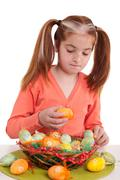 beautiful little girl decorate the basket with easter eggs - stock photo