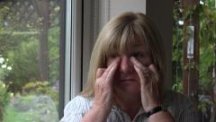 Lonely senior woman with headache takes off glasses and rubs eyes and temple Arkistovideo