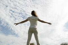 Woman with arms outstretched , cloudy sky in background, rear view Stock Photos