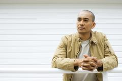 Man leaning against railing with clasped hands, looking away - stock photo