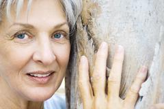 Stock Photo of Senior woman leaning against tree trunk, smiling at camera, close-up