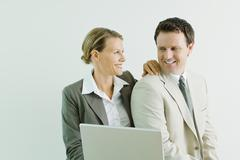 Male and female business associates together, smiling at each other - stock photo